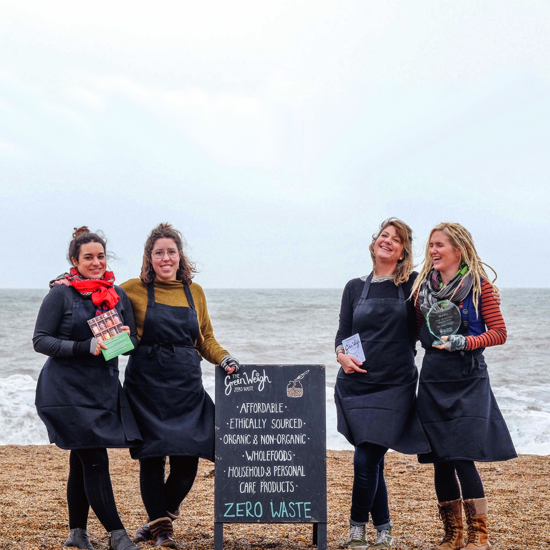 The four Green Weigh ladies next to their shop sign on the beach