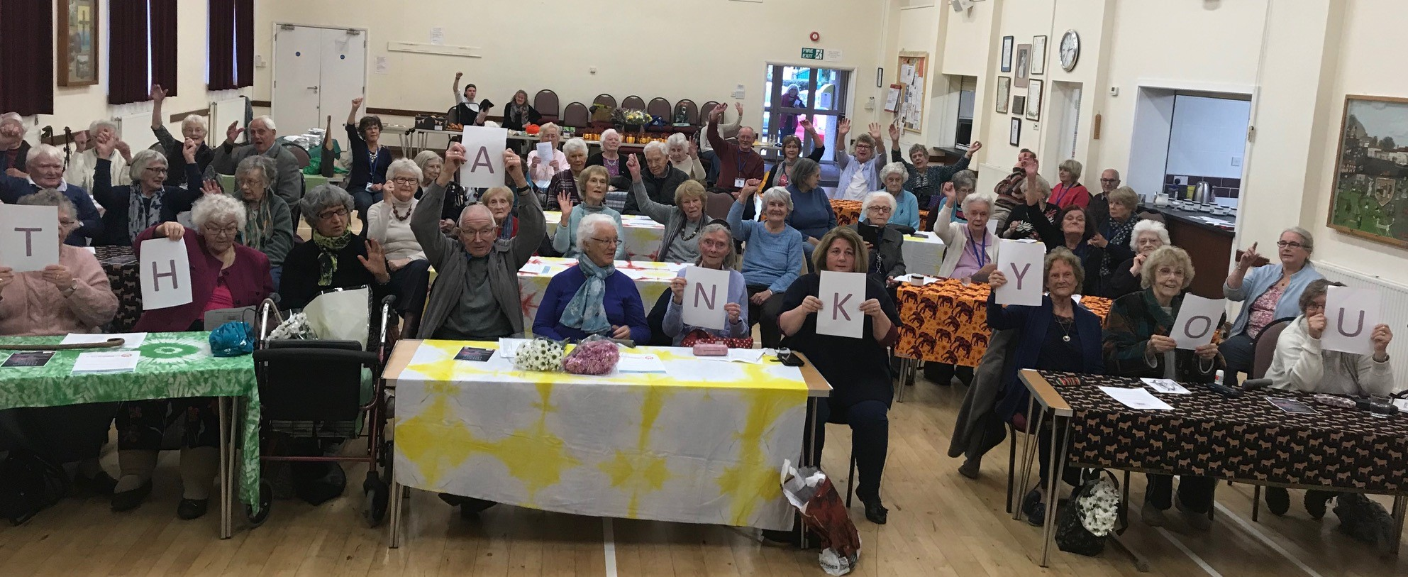 A group of elderly members of Rotherfield St Martin (RSM) hold up letters spelling out 'thank you'.