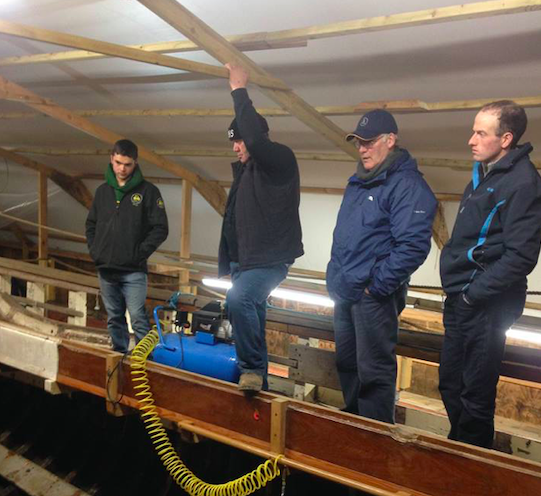 A group of men looking down at the Britannia which they are restoring