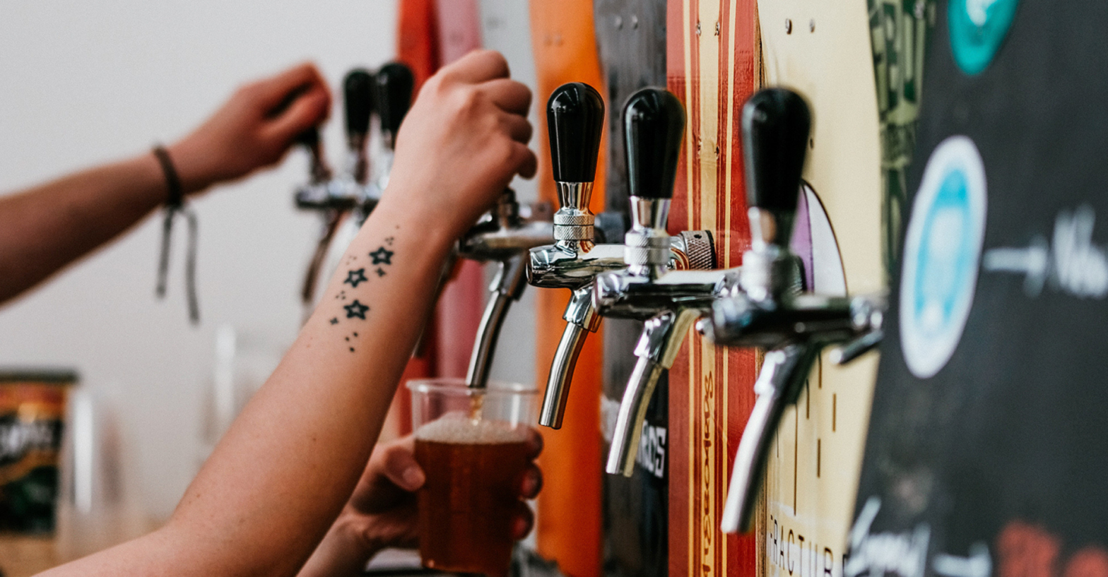 A hand pouring a pint in a brewery