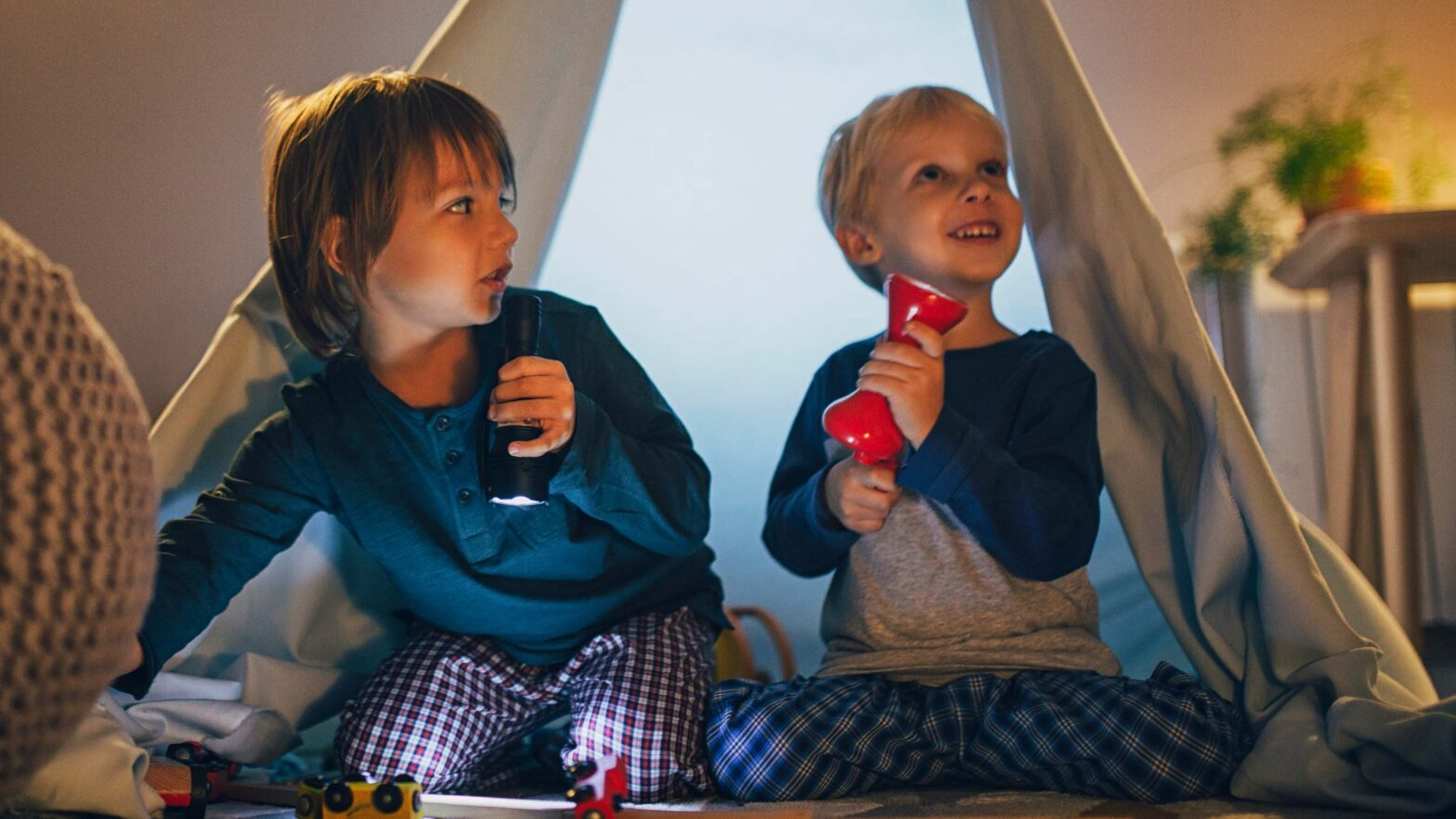 Two young children playing in a tent